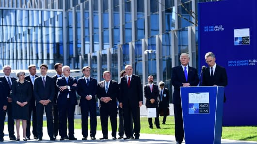 US President Donald Trump listens to NATO Secretary General Jens Stoltenberg's speech during the unveiling ceremony of the Berlin Wall monument, during the NATO summit