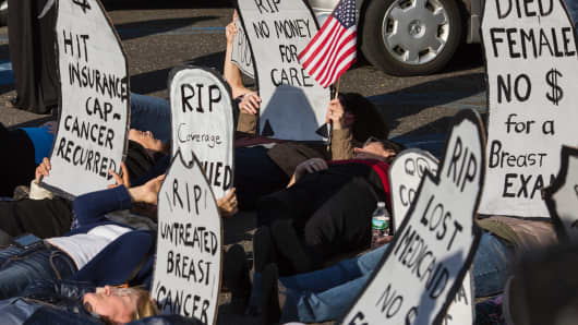 Protesters stage a 'die-in' before a town hall meeting with US Representative Tom MacArthur (R-NJ) in Willingboro, New Jersey on May 10, 2017. MacArthur wrote the amendment to the American Health Care Act that revived the failed bill, delivering a legislative victory for US President Donald Trump.