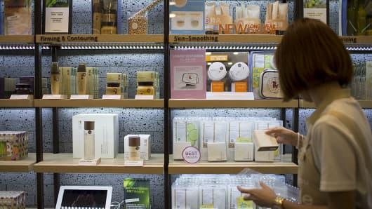 An employee stocks shelves in an Amorepacific Innisfree brand store in Causeway Bay, Hong Kong.