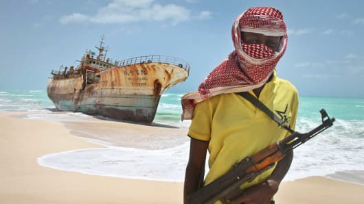 A masked Somali pirate stands near a Taiwanese fishing vessel that washed up on shore after the pirates were paid a ransom and released the crew, in the once-bustling pirate den of Hobyo, Somalia.