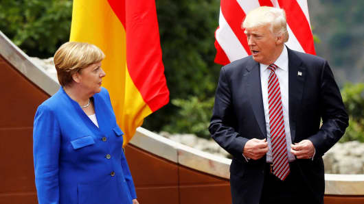 German Chancellor Angela Merkel (L) and U.S. President Donald Trump (R) attend the group photo in the ancient amphitheater at the G7 Taormina summit on the island of Sicily in Taormina, Italy on May 26, 2017.