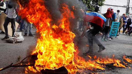 Opposition supporters set up a burning barricade during clashes with security forces at a rally against Venezuela's President Nicolas Maduro in Caracas, Venezuela May 20, 2017.