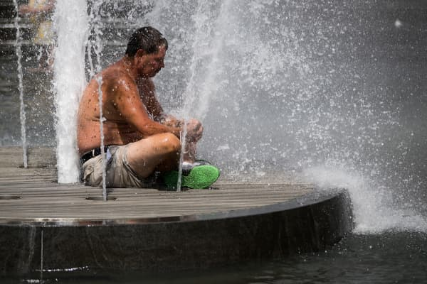A man keeps cool as he sits in the fountain at Washington Square Park in New York City.