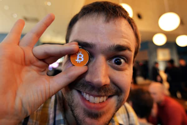 A member of a Bitcoin trading club posing with a Bitcoin medal at the club's meeting in Tokyo.
