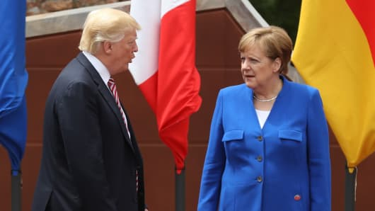 German Chancellor Angela Merkel and U.S. President Donald Trump arrive for the group photo at the G7 Taormina summit on t