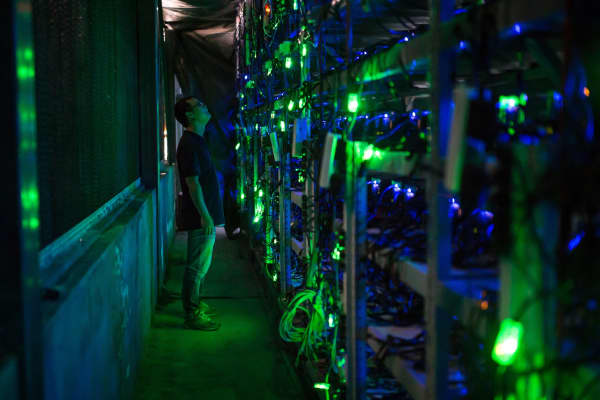 Haobtc's bitcoin mine site manager, Guo-hua, checks mining equipment inside their bitcoin mine near Kongyuxiang, Sichuan, China.