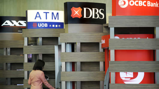 A customer uses a DBS automated teller machine (ATM), standing between the ATMs of United Overseas Bank and Oversea-Chinese Banking Corp.