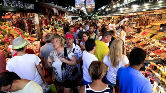 Tourists and pedestrians fill an aisle between food stalls inside Boqueria market in Barcelona, Spain.