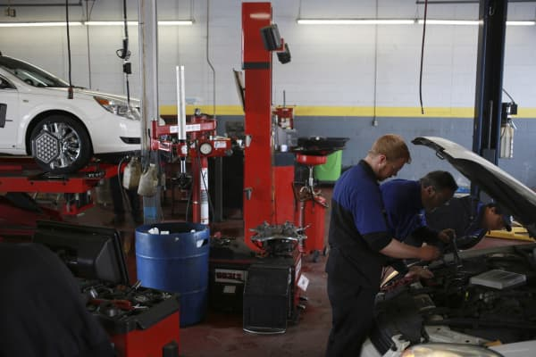 Service technicians work under the hood of a customer's vehicle.