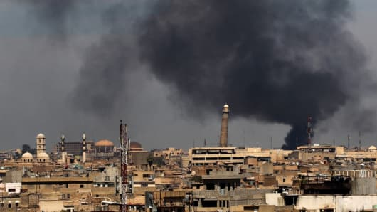 Smoke billows from behind the Great Mosque of al-Nuri in Mosul's Old City on April 17, 2017, during an offensive by Iraqi security forces to recapture the city from Islamic State.