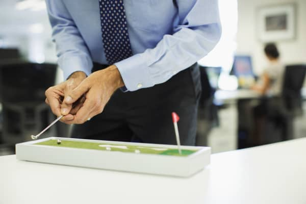 A businessman plays with a toy golf set in the office.