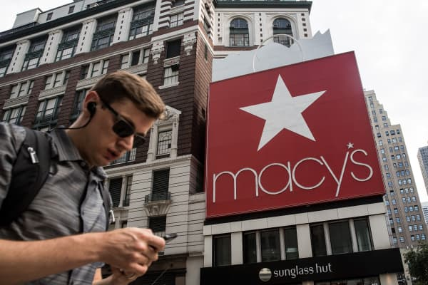 A man checks his phone as he walks past Macy's flagship store in New York City.