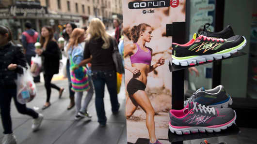 Pedestrians walk past Skechers shoes displayed outside of a store in San Francisco, California.