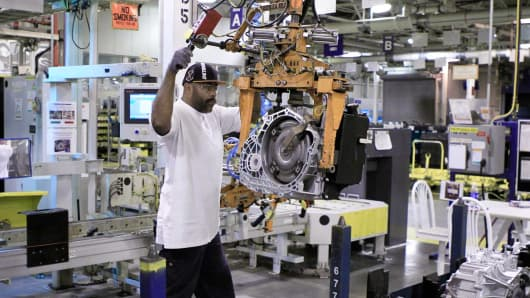 An employee removes a finished transmission from the assembly line at the General Motors transmission plant in Warren, Michigan.
