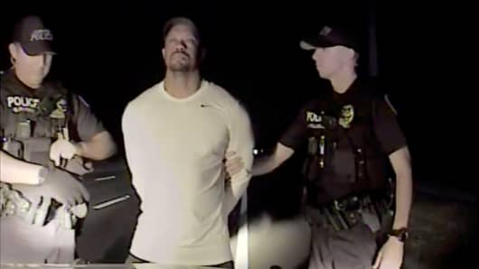 Tiger Woods is seen handcuffed and searched by police officers in this still image from police dashcam video in Jupiter, Florida, U.S. on May 29, 2017.