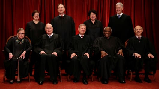 Chief Justice John Roberts (seated C) leads Justice Ruth Bader Ginsburg (front row, L-R), Justice Anthony Kennedy, Justice Clarence Thomas, Justice Stephen Breyer, Justice Elena Kagan (back row, L-R), Justice Samuel Alito, Justice Sonia Sotomayor, and Associate Justice Neil Gorsuch in taking a new family photo including Gorsuch, their most recent addition, at the Supreme Court building in Washington.