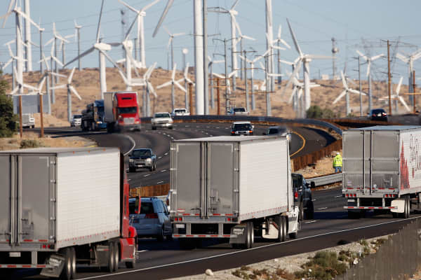 Emissions-producing diesel trucks and cars pass non-polluting windmills along the 10 freeway on December 8, 2009 near Banning, California.