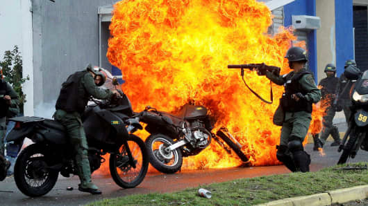 Security forces clash with demonstrators as a motorcycle is set on fire during a protest against Venezuelan President Nicolas Maduro's government in San Cristobal, Venezuela May 29, 2017.