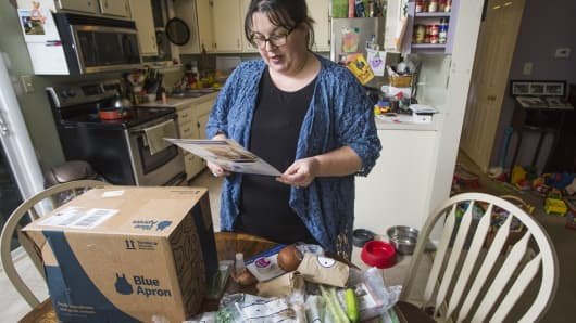 Emily Griffin reads a recipe for a Blue Apron meal while unpacking her box at her Lisbon Falls home on Tuesday, Dec. 6, 2016.