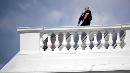 A Secret Service officer stands guard on the roof of the White House following a temporary lock down May 31, 2017 in Washington, DC.