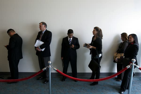 Job searchers stand in line during a career fair.