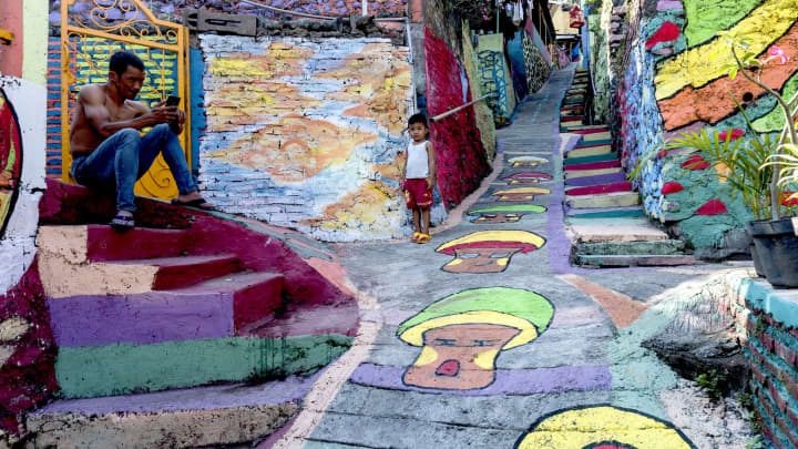 Villagers relax along a path at an Indonesian hamlet dubbed 'the rainbow village' in Semarang, central Java.