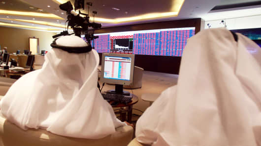 Traders monitor screens displaying stock information at Qatar Stock Exchange in Doha, Qatar June 5, 2017.