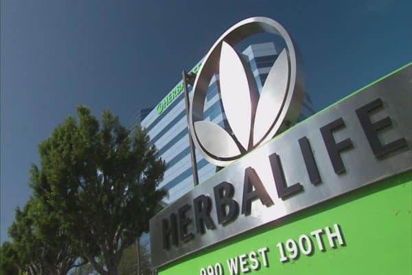 Herbalife cuts sales guidance; exceeds key FTC mandate