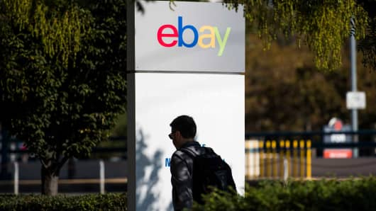 An employee walks past eBay signage at the company's headquarters in San Jose, California.
