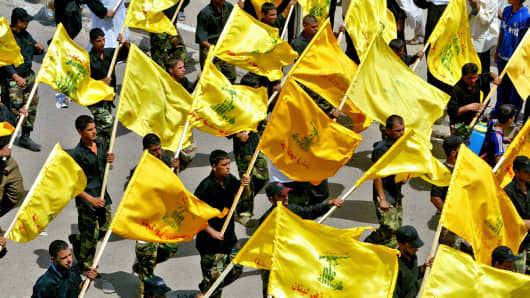 Members of the Shiite Mehdi army militia carry Lebanese Hezbollah flags as they rally in Baghdad's neighborhood of Sadr City in 2006.