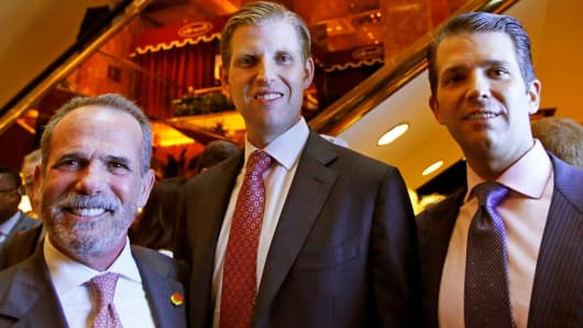 Eric Danziger, CEO of Trump Hotels, left, joins Eric Trump, center, and Donald Trump Jr., both of whom are executive Vice Presidents of The Trump Organization, as the trio poses for a photograph during an event for Scion Hotels, Monday, June 5, 2017, in New York.