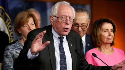 Sen. Bernie Sanders speaks to reporters as Senate Democratic Leader Chuck Schumer (2nd R) and House Democratic Leader Nancy Pelosi (R) look on.