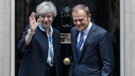 Theresa May, U.K. prime minister, left, waves as she stands with Donald Tusk, president of the European Union (EU), outside number 10 Downing Street in London, on Thursday, April 6, 2017