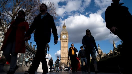People walk near the Elizabeth Tower, commonly referred to as Big Ben, near the Houses of Parliament in Westminster, central London on April 18, 2017.