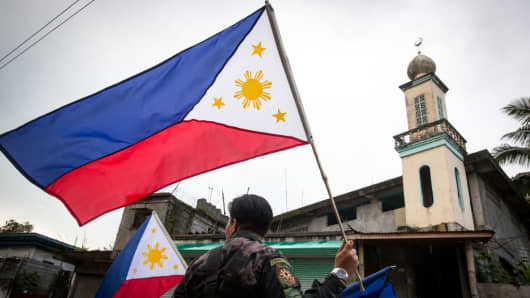 The Philippine National Police hang flags in war-torn Marawi City in preparation for the celebration of Independence Day on June 12.