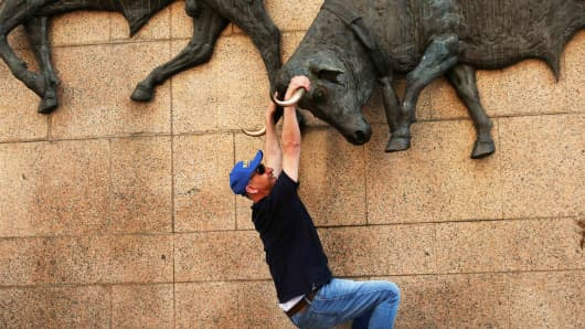 A man has his photo taken hanging from a bull sculpture outside Las Ventas bullring during San Isidro's bullfighting fair in Madrid, Spain.