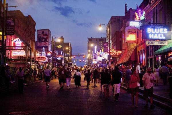 Pedestrians walk down Beale Street at dusk in downtown Memphis.