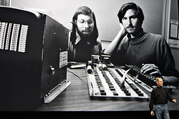 Steve Jobs in front of a picture of himself and Apple co-founder Steve Wozniak
