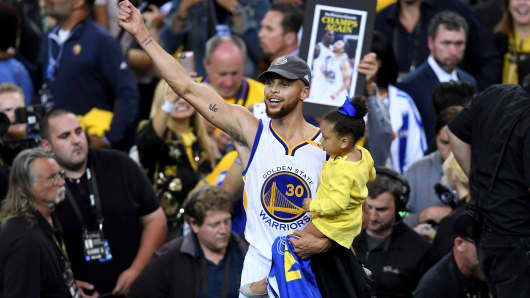 Stephen Curry #30 of the Golden State Warriors celebrates holding his daughter after defeating the Cleveland Cavaliers 129-120 in Game 5 to win the 2017 NBA Finals at ORACLE Arena on June 12, 2017 in Oakland, California