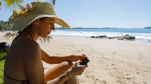 Holidaymaker uses her phone at the beach