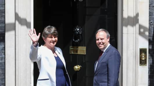 Arlene Foster, leader of the Democratic Unionist Party (DUP), left, waves as Nigel Dodds, deputy leader of the Democratic Unionist Party (DUP), looks on as they pose for photographers on the steps of number 10 Downing Street, during their arrival for a meeting with U.K. Prime Minister Theresa May, in London, U.K., on Tuesday, June 13, 2017.