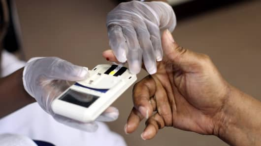 A mans finger is pricked to test cholesterol and blood sugar.