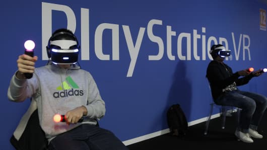 A visitor plays a video game with a virtual reality head-mounted headset 'PlayStation VR' developed by Sony Interactive Entertainment.