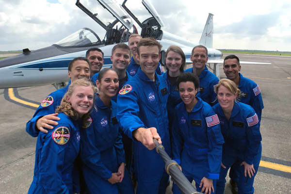 NASA's 2017 astronaut candidates stop to take a group photo while getting fitted for flight suits at Ellington Field near NASA's Johnson Space Center in Houston.