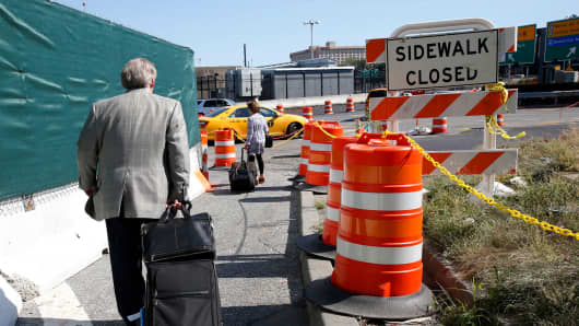 Arriving passengers haul their suitcases down a pathway toward temporary taxi stand outside of Terminal B at LaGuardia Airport in New York.
