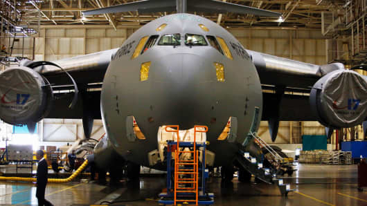 An employee works inside the cockpit of a C-17 Globemaster III military cargo jet being manufactured for the Indian Air Force.