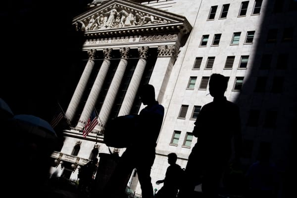 The silhouettes of pedestrians are seen passing in front of the New York Stock Exchange in New York.