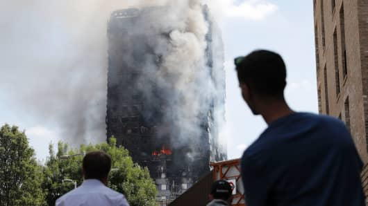 Pedestrians look up towards Grenfell Tower, a residential block of flats in west London on June 14, 2017, as firefighters continue to control a fire that engulfed the building in the early hours of the morning. Shaken survivors of a blaze that ravaged a west London tower block told Wednesday of seeing people trapped or jump to their doom as flames raced towards the building's upper floors and smoke filled the corridors.