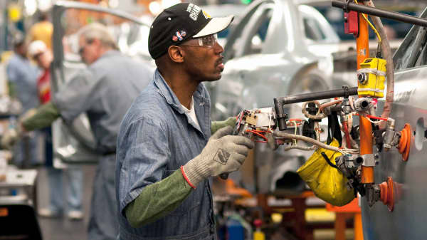 Workers install doors on Chevrolet Malibu and Buick LaCross vehicles at the General Motors plant in Fairfax, Kansas.