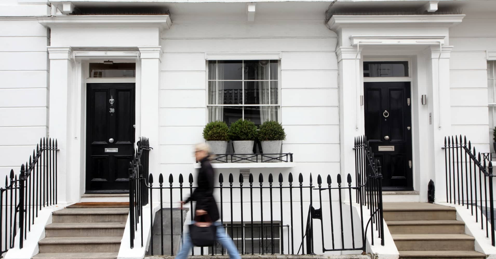 A pedestrian passes luxury residential properties in Knightsbridge in London, U.K.